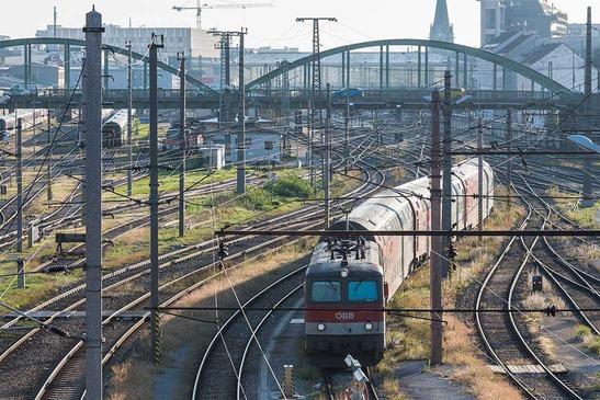 Rail tracks with train leaving a city