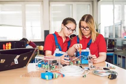 Zwei Lehrlinge schrauben an einem Elektronikteil