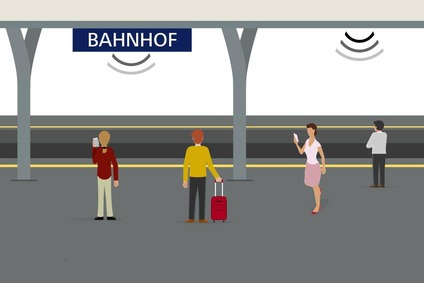 Das Bild zeigt einen Bahnsteig mit Bahnsteigdach und Menschen, die das Service WLAN am Bahnhof nutzen.