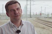 Das Bild zeigt einen Mann, im Hintergrund sieht man Gleise und Signale