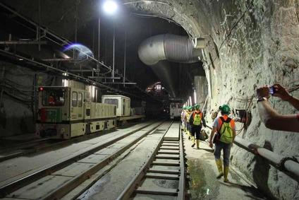 Blick in einen Tunnel mit Bauzug, mehreren Gleisen und Exkursionsteilnehmern