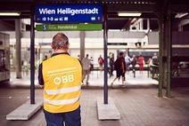 Auf einem Bahnsteig steht ein ÖBB Mitarbeiter mit Warnweste und beobachtet die Fahrgäste, die sich im Hintergrund bewegen