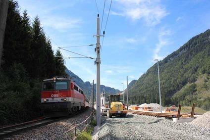 Blick auf einen Zug auf der Pyhrnstrecke und auf Bauarbeiten bei laufendem Betrieb