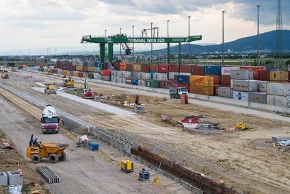Blick auf das Baufeld mit Baufahrzeugen, im Hintergrund Containerkran mit Containern