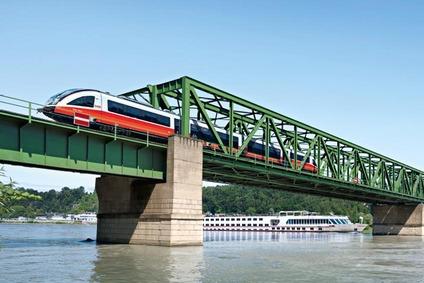 Sujet für Regionalbahnkampagne Donauuferbahn, Eisenbahnbrücke mit Zug und Schiff am Wasser