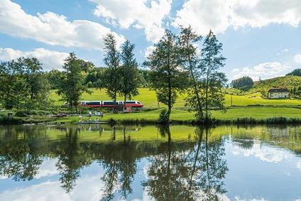 Zug fährt durch Hügellandschaft mit kleinem See
