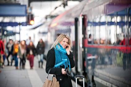 Woman holding her mobile at the station platform.