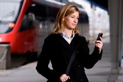 Woman holding a telephone, a train passing in the background.