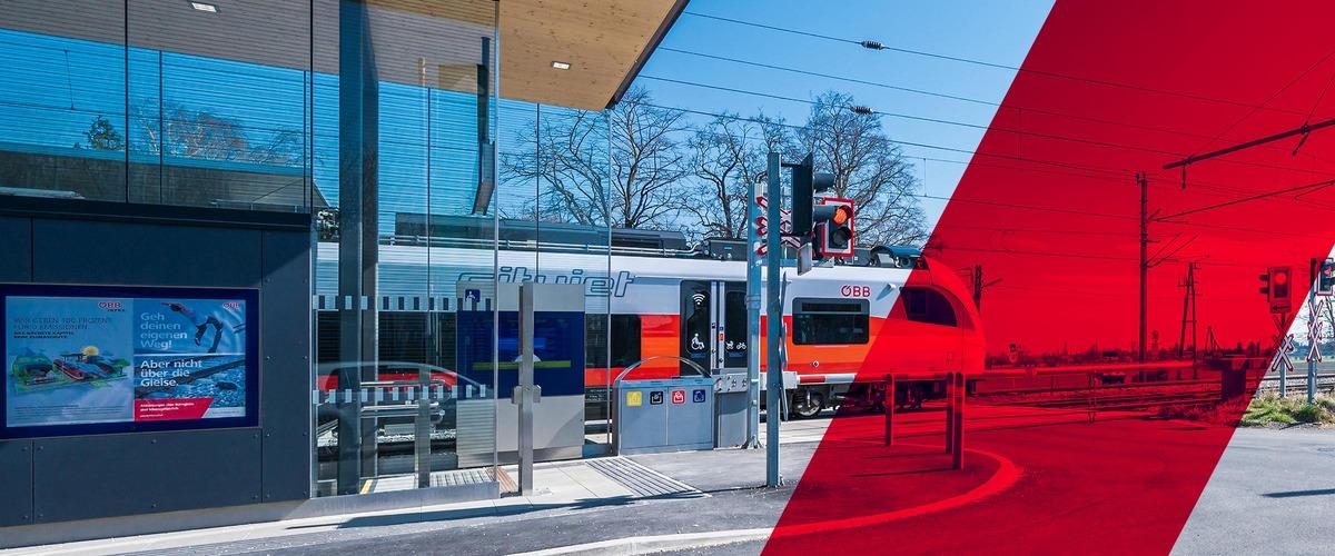 Regionalzug passiert Eisenbahnkreuzung. Der Schranken ist geschlossen, die Lichtzeichenanlage leuchtet Rot