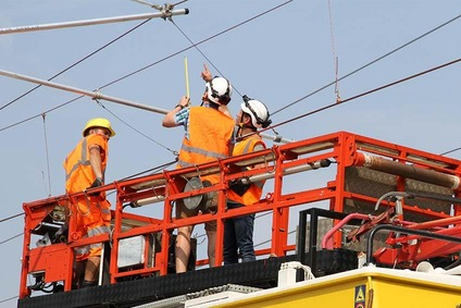 Workers on a lifting platform installing a catenary