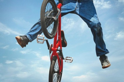 Teenager jumping up with a bicycle
