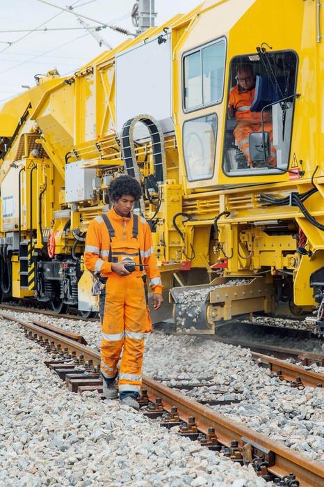Zwei spezifisch ausgebildete Facharbeiter führen Reparaturarbeiten, an mehreren Gleiskörpern, durch.