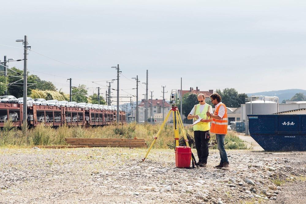 Zwei Fachkräfte vermessen ein potenzielles Baugebiet.