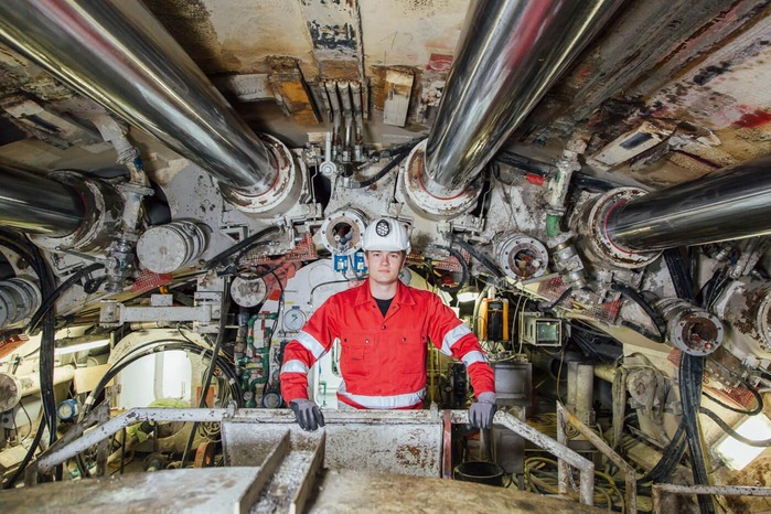 A mechanic takes care of the functionality of a tunnel drilling machine.