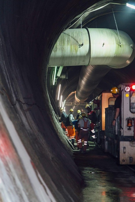 Several miners are transported out of the tunnel by train.