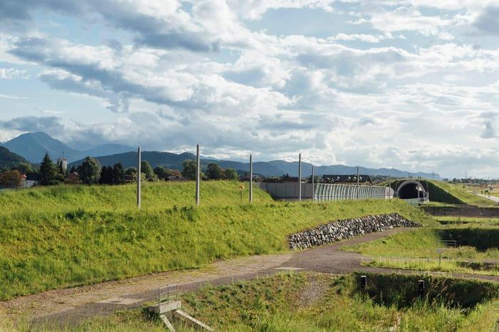 Das Foto zeigt einen Eisenbahntunnel der sich ideal in die umliegenden Gegebenheiten einfügt.