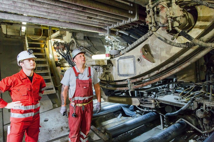 Two mechanics check the functionality of a tunnel drilling machine.