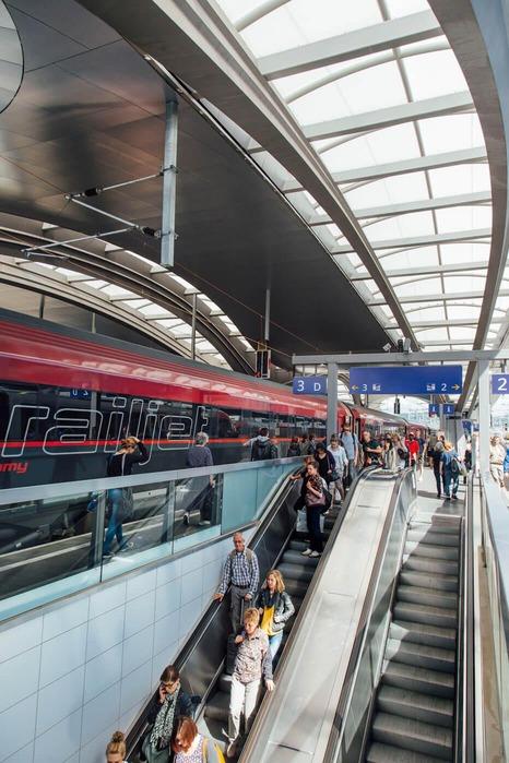 Ein Railjet steht abfahrbereit am Bahnsteig.