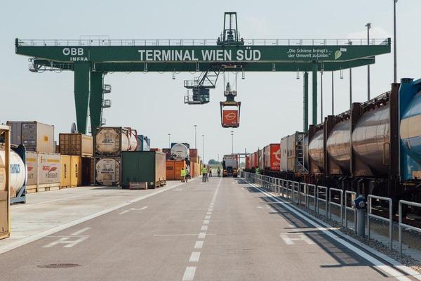 Ein Portalkran verlädt mehrere Container auf ein Lastkraftfahrzeug.
