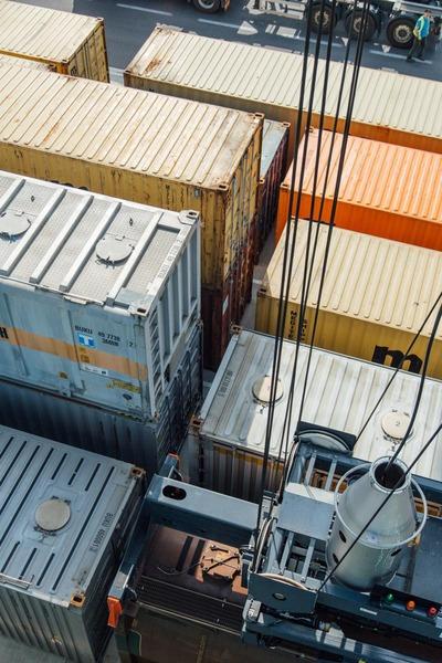 Ein Portalkran hebt einen Container hoch.