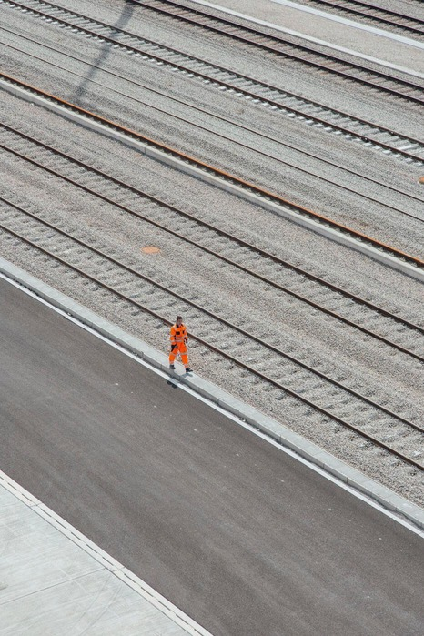Ein Mitarbeiter marschiert eine Eisenbahnstrecke entlang.