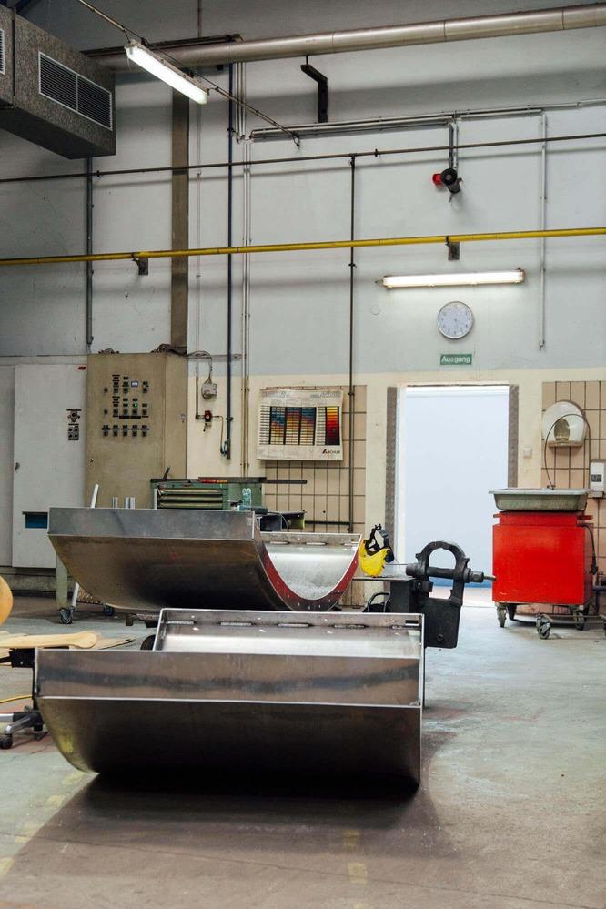 In einer Lagerhalle lagern die bereits geformten Metallteile.