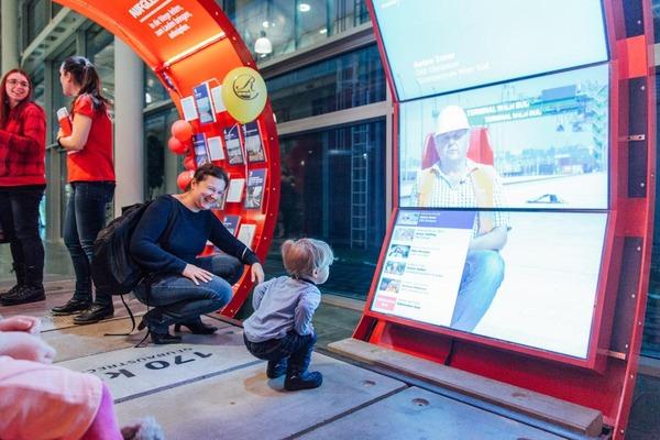 """Ein kleiner Junge steht fasziniert vor einem Bildschirm der """"InfoRail"""" Ausstellung."""