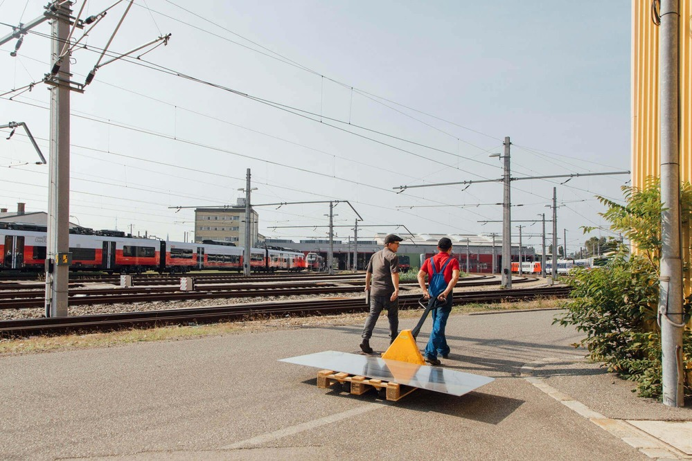 """Zwei Konstrukteure transportieren benötigtes Material für die """"InfoRail"""" - Röhre."""