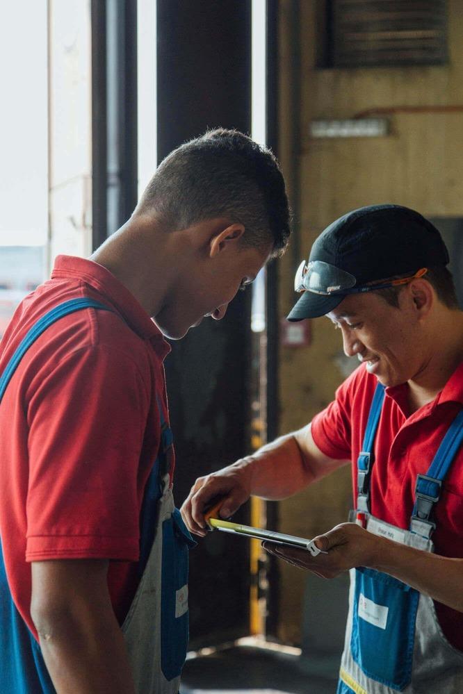 Zwei Lehrlinge messen die produzierten Metallstücke ab.
