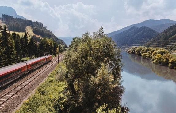 Ein Zug fährt entlang eines Flusses.