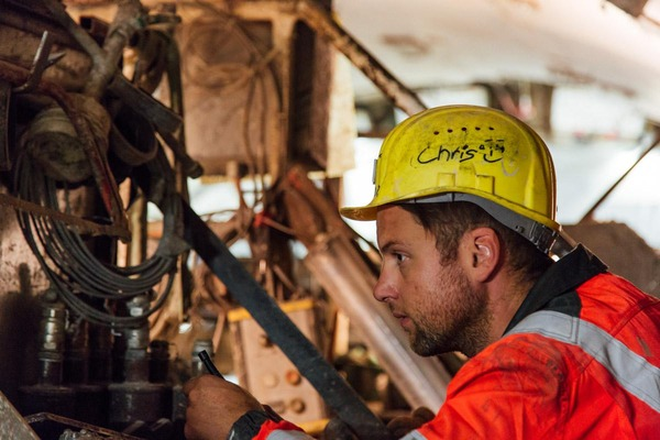 A mechanic checks the technical functionality of a tunnel drilling machine.