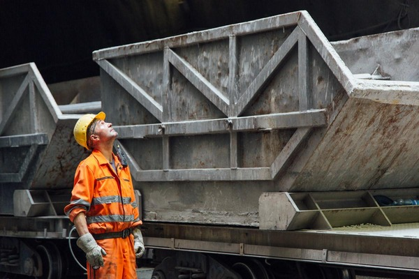 A miner controls the loading process of a train.