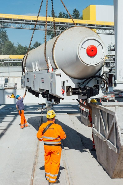 A crane lifts a cement transport container onto the tracks.