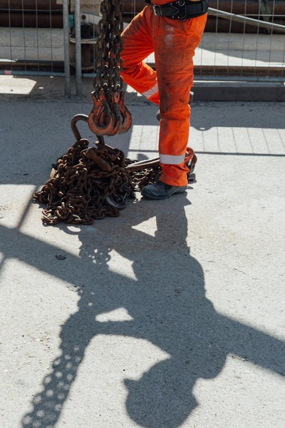 An employee untangles several metal chains.