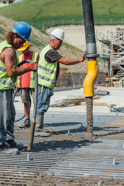 Several construction workers fill an area with cement.