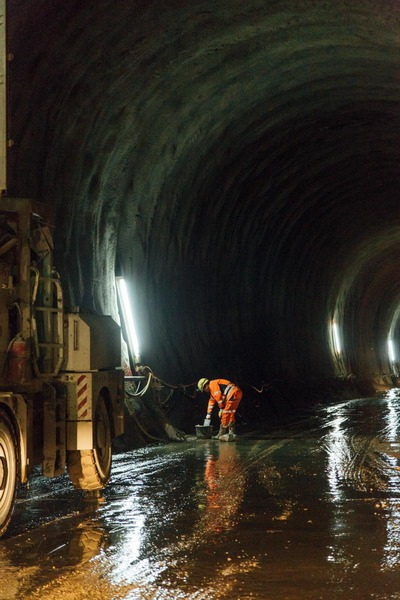 A miner checks a tunnel wall.