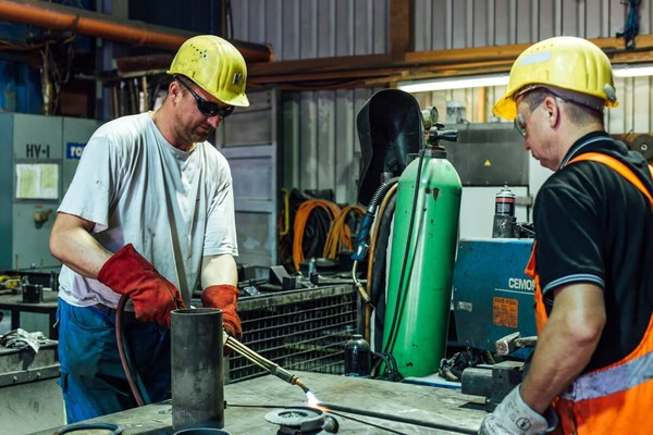 Two skilled workers weld the required parts together.