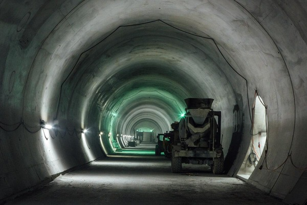 Several construction machines are parked in a tunnel tube.