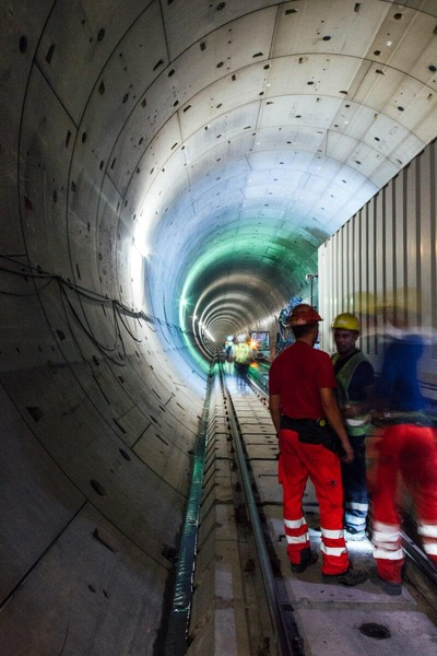 Several tunnel construction workers discuss the further course of work.
