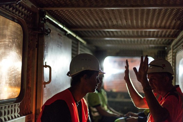 Two miners ride in a rescue train and talk about their working day.