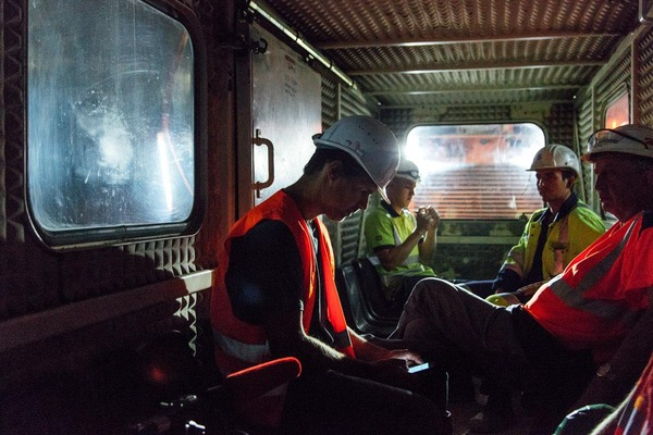 Several miners ride in a rescue train and talk about their working day.