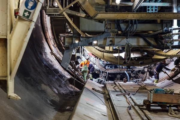 Several mechanics repair the drill head of a tunnel drilling machine.