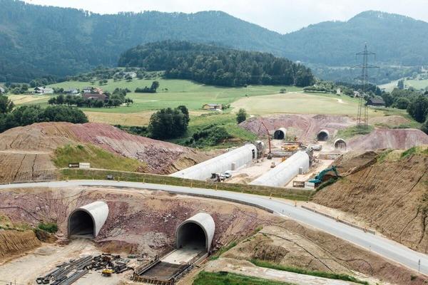 Several miners are working on the construction of two exposed tunnel tubes.