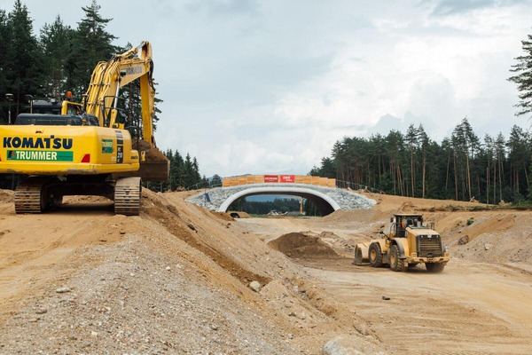 An excavator and a wheel loader remove superfluous soil.