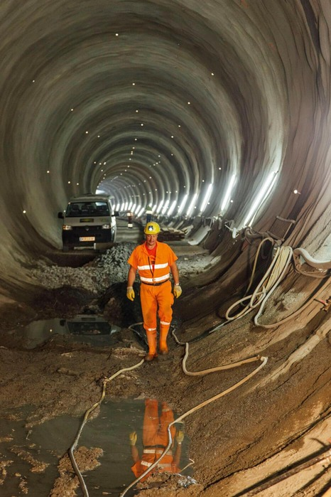 A miner walks along a tunnel tube.