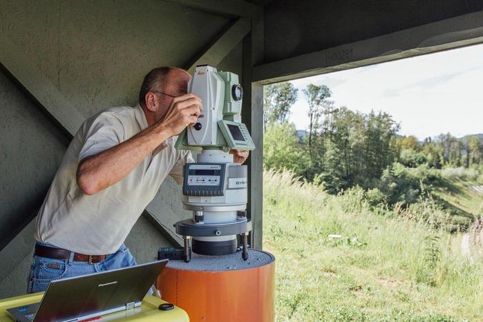 A surveyor measures the surrounding landscape.