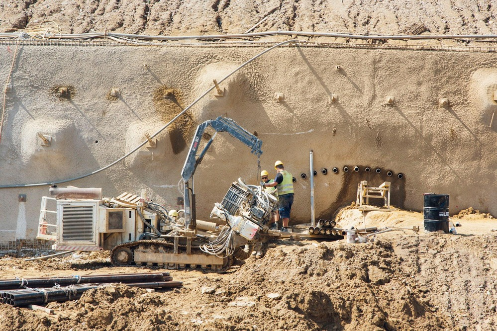 Two miners control the outer layer of a tunnel wall.