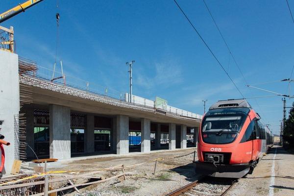 A passenger train passes a construction site.