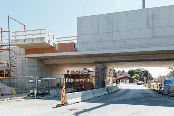 Several construction workers are working on the completion of a railway bridge.