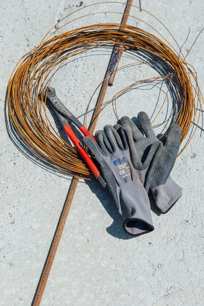 Gloves of construction worker on wire sling